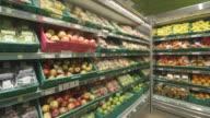 POV shot moving across shelves of fruit in a supermarket.