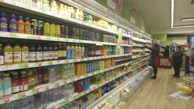 POV shot moving past a large refrigerator of soft drinks in a supermarket.