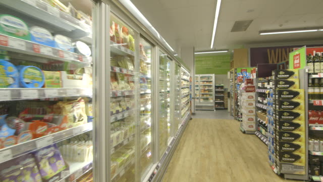 POV shot moving past refrigerator cabinets in a supermarket.