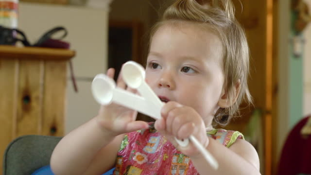 CU Shot of 14 month-old toddler plays with measuring spoons / Manistique, Michigan, United States