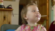 CU Shot of 14 month-old toddler sucks on an empty measuring spoon / Manistique, Michigan, United States
