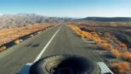 POV shot of 4x4 car driving on long straight road through the desolate Atacama desert mountains