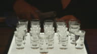 Shot of a bartender filling up a tray of shot glasses.