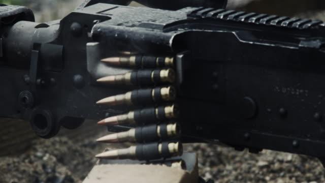 Shot of a belt-fed machine gun as it is fired.
