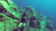 MS PAN POV Shot of A diver films rocky ocean floor where Costa Concordia accident happened / Giglio Porto, Tuscany, Italy