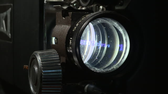 CU shot of a Eike 16mm film projector lens.  The lens flickers while the footage goes through the frame.