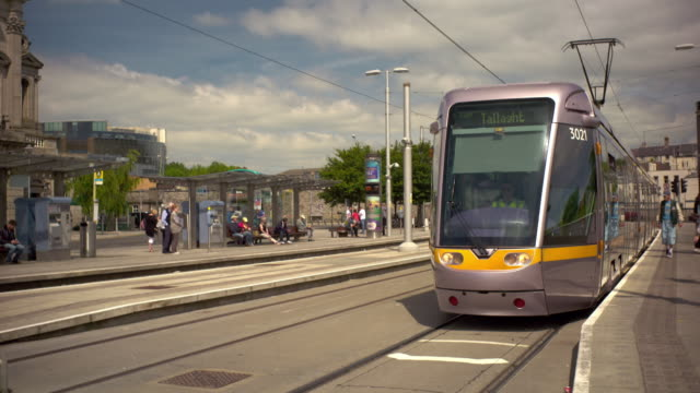 Shot of a Luas train pulling up to the station in Dublin, Ireland. Passengers get off and on the train.