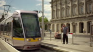 Shot of a Luas train pulling up to the station in Dublin Ireland on a summer day