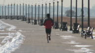 Shot of a man jogging through Liberty State Park on a cold winter day.