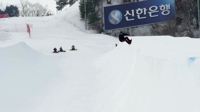 Shot of a person snowboarding on halfpipe at ski resort