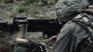 Shot of a soldier firing a belt-fed machine gun from a sitting position.
