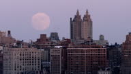 Shot of a very large moon next to the San Remo Apartments in Manhattan.  Shot encompasses a section of the Midtown Manhattan Skyline