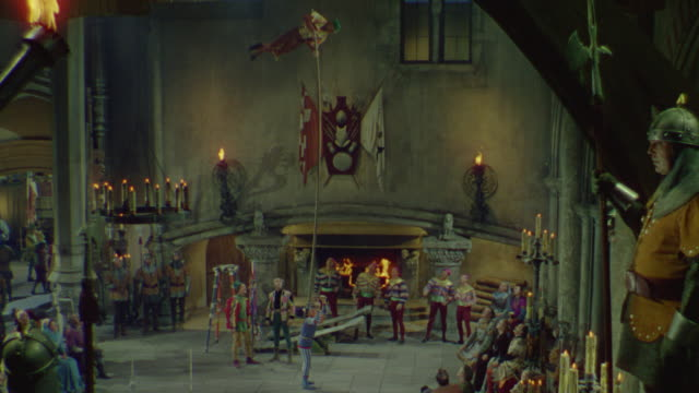 WS Shot of acrobats performing inside castle in front of audience