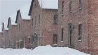 MS PAN Shot of across building at Auschwitz with tourists walking through with snow rain / Auschwitz-Birkenau, Krakow, Poland