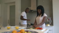 MS ZI ZO Shot of African couple preparing and cooking food in kitchen / Cape Town, Western Cape, South Africa