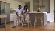 WS ZI ZO Shot of African man and woman sitting in kitchen talking and drinking coffee, woman reading magazine  / Cape Town, Western Cape, South Africa