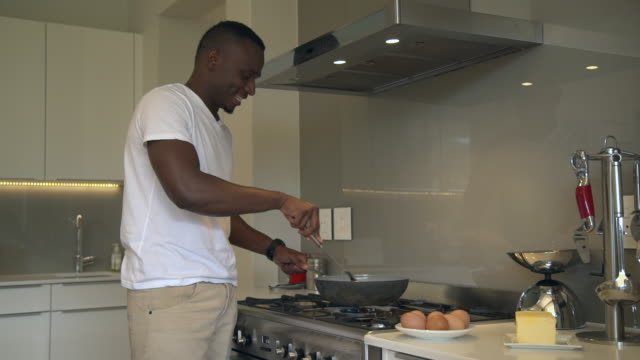 MS ZI ZO Shot of African man cooking in kitchen / Cape Town, Western Cape, South Africa