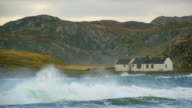MS Shot of agitated waves with hills with house and clouds / Drumbeg, Scotland, United Kingdom