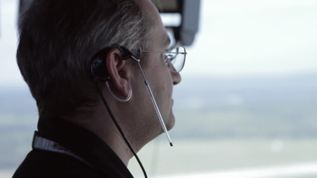 CU Shot of air traffic controller wearing ear piece and mic looking through binoculars in air traffic control tower / Sterling, Virginia, United States
