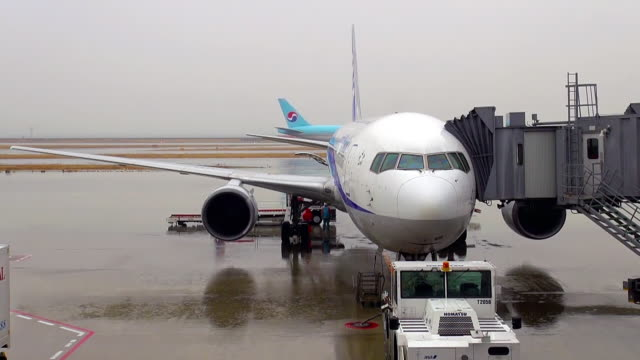 MS Shot of Airplane loading at gate on rainy day at Kansai Airport / Osaka, Osaka Prefecture, Japan