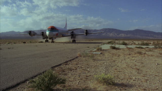 MS Shot of airplane on runway in desert and military jeep following