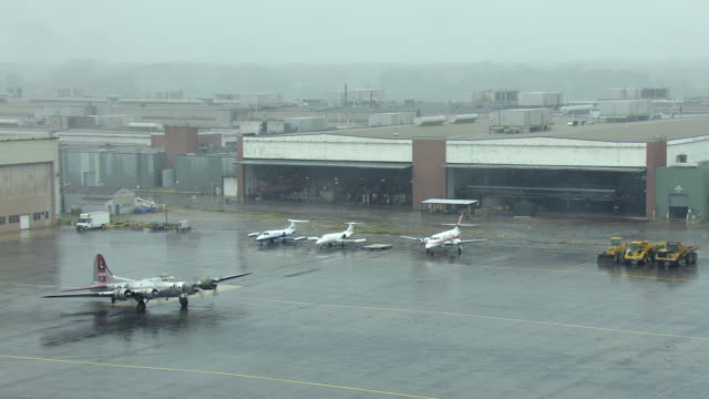 MS AERIAL Shot of airplanes siting on parking lot in mist and propellers going / Ypslanti, Michigan, United States