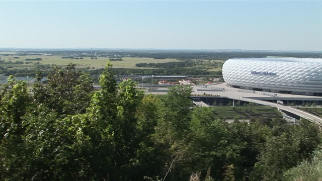WS PAN Shot of Allianz Arena building surrounded by tree / Munich, Bavaria, Germany