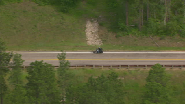 MS AERIAL TS Shot of alongside bikers riding highway 170 through forested area / Sturgis, South Dakota, United States