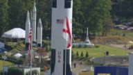 MS AERIAL Shot of American flags with Saturn V Rocket outside on display and Davidson Center for Space Exploration / Huntsville, Alabama, United States