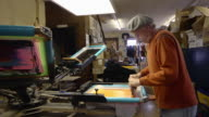 MS Shot of an artisian pulling ink over a silk screen to print designs on a shirt / Ann Arbor, Michigan, United States