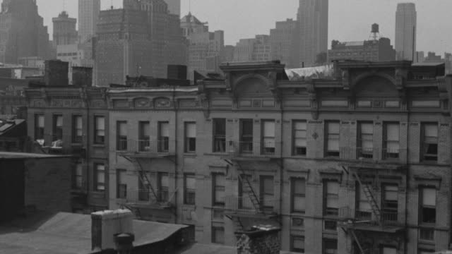 MS TU Shot of apartment building along fire escape to overlooking New York City skyline
