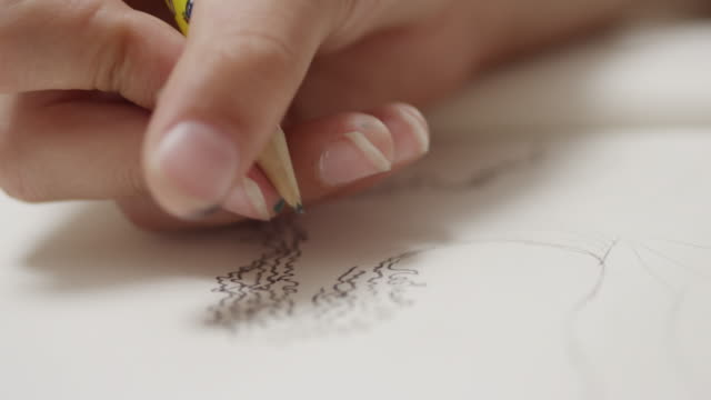 CU Shot of artist drawing with pencil on paper / London, Hampstead, United Kingdom