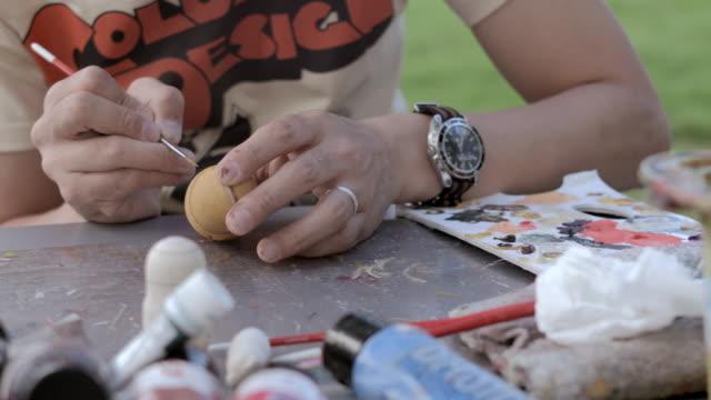 CU Shot of artist making Matryoshka doll at the park / Nerima, Tokyo, Japan