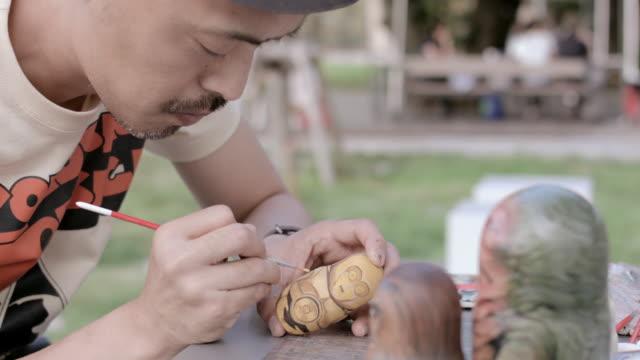 CU PAN Shot of Artist making Matryoshka doll at the park / Nerima, Tokyo, Japan