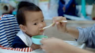 MS Shot of asian mother spoon feeding her son at home