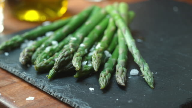 CU PAN SLO MO Shot of Asparagus being served onto slate / United Kingdom