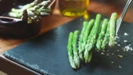 CU SLO MO Shot of Asparagus being served onto slate / United Kingdom