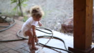 MS Shot of baby boy playing with water hose / Santa Fe, New Mexico, United States