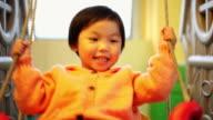 CU Shot of baby girl playing on swing / Xian, China