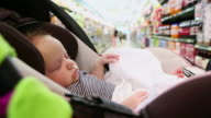 MS POV Shot of baby sleeping in grocery cart moving down aisles / Santa Fe, New Mexico, United States