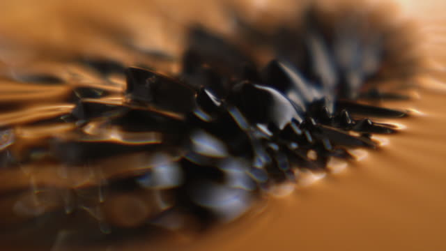 ECU SLO MO Shot of backlit orange magnetic ferris fluid, ferro fluid / Studio, New York, United States