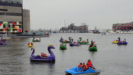 MS Shot of Baltimore Maryland Inner harbor with families out of dragon boats peddling for fun on Chesapeake Bay / Baltimore, Maryland, United States