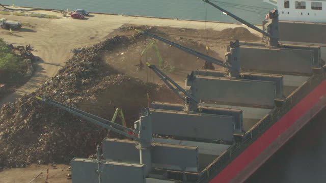 MS AERIAL Shot of barge being filled with trash / Port of Tampa, Florida, United States