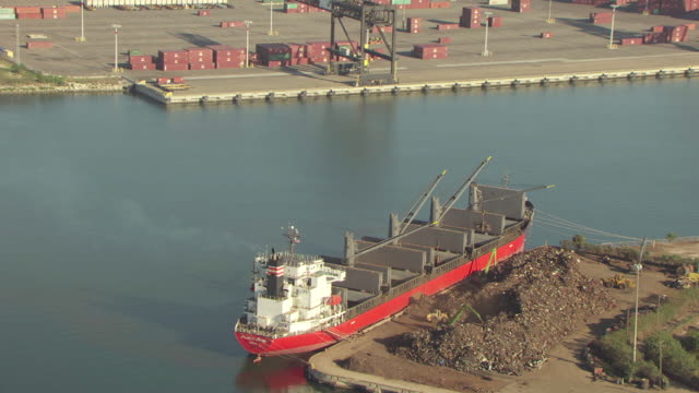 MS AERIAL ZO Shot of barge being filled with water and land / Port of Tampa, Florida, United States