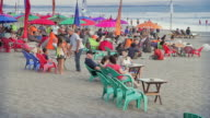 MS Shot of Beach culture and tourists relaxing beneath umbrellas on beanbags on beach at dusk / Seminyak, Bali, Indonesia