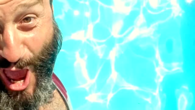 SELFIE shot of bearded man jumping into the pool