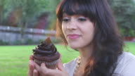 CU Shot of beautiful brunette eating chocolate cupcake in park / Portland, Oregon, United States