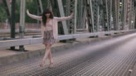 MS TS SLO MO Shot of beautiful brunette playfully walking along bridge while traffic drives behind her / Portland, Oregon, United States
