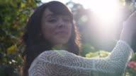 CU SLO MO TS Shot of beautiful brunette smiles and smells rose on sunny day / Portland, Oregon, United States