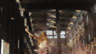 'MS LA SLO MO Shot of Beautiful woman popping big balloon in abandoned building / Berlin, Germany'